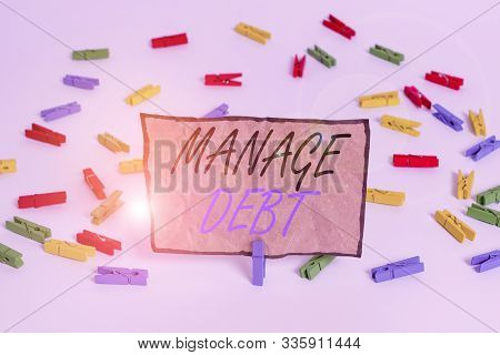 Handwriting text writing Manage Debt. Concept meaning unofficial agreement with unsecured creditors for repayment Colored clothespin papers empty reminder white floor background office. poster