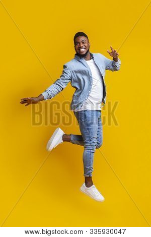 Portrait of funny black man jumping on yellow background with euphoric face expression, free space for text poster