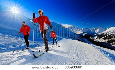 A family group of cross country skiers on a sunny winter morning in Swiss Alps, 4 Valleys Thyon, Switzerland.