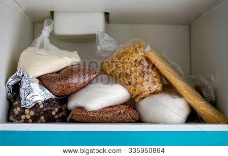 Unorganized Storage Of Cereals In The Kitchen Cabinet. Macaroni, Sugar, Buckwheat, Corn Balls In Sac