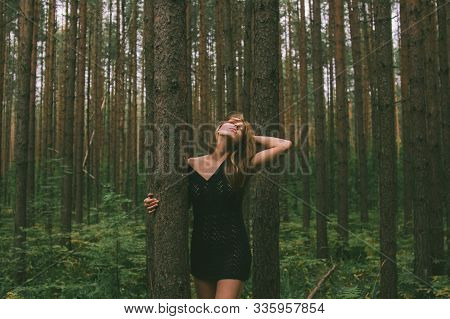Portrait Of Young Beautiful Girl In Black Dress With Threw Back Head In Forest That Holds Tree Trunk