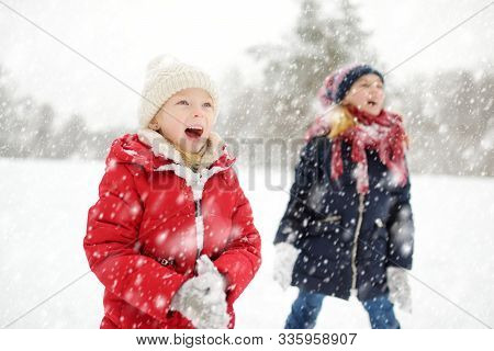 Two Adorable Young Girls Having Fun Together In Beautiful Winter Park. Cute Sisters Playing In A Sno