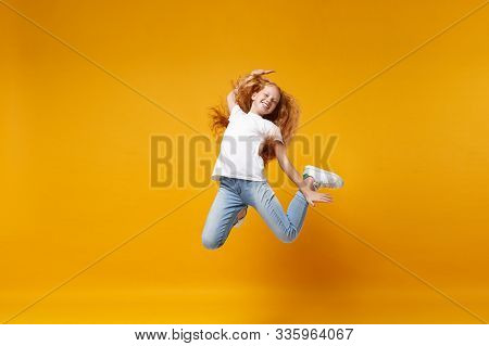 Cheerful Little Ginger Kid Girl 12-13 Years Old In White T-shirt Isolated On Yellow Background Child