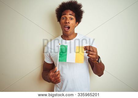 Young african american man holding Ireland Irish flag standing over isolated white background scared in shock with a surprise face, afraid and excited with fear expression