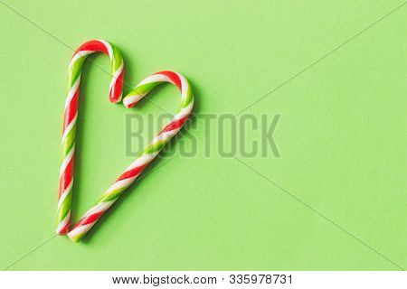 Two Candy Canes Making A Heart On A Red Textured Background. Candy Cane Heart. Christmas Candy Canes