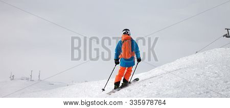 Skier Before Downhill On Snowy Freeride Slope And Overcast Misty Sky At Day With Bad Weather Before