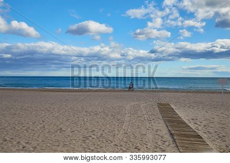Lonely Sandy Beach With A Lifeguard And A Boardwalk To The Sea On The Costa Blanca Spain