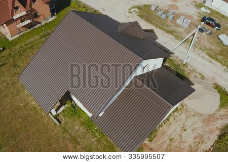 Modern Roof Made Of Metal. Brown Metal Tile On The Roof Of The House. Corrugated Metal Roof And Meta