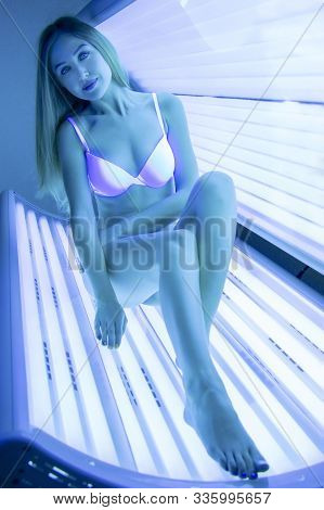 Beautiful Slender Blonde Sunbathes In The Solarium. A Girl In A Gorizontal Tanning Bed Sitting And S