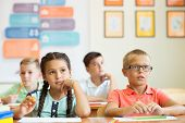 Clever schoolchildren studing and answer questions in classroom at school poster