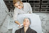 Female cosmetologist making oxygen mesotherapy to a woman at the luxury beauty salon. Concept of a professional facial treatment poster