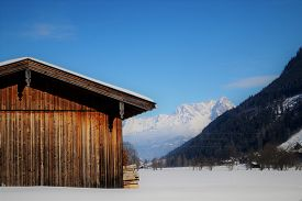 Alpine Barn. A Weathered Wooden Barn Sits In A Snow-covered Field Among The Alps. Location: Zell Am