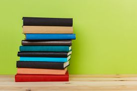 Simple Simple Composition Of Many Hardback Books, Unprocessed Books On A Wooden Table And A Green Ba
