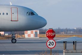Stop Sign On The Road Service Vehicles On The Platform Of The Airport, The Aircrafts Nose