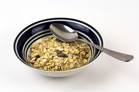 Blue bowl of oat cereal with spoon