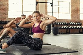 Fitness young woman doing abs crunches. Portrait of a determined girl doing sit ups in fitness center with man and woman. Fit class at gym doing abdominals workout on yoga mat with copy space.