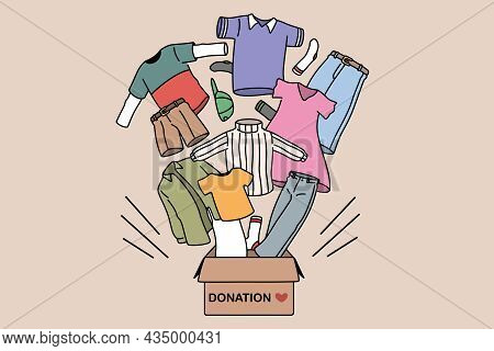 Charity And Donating Clothes Concept. Box With Donation Word And Carious Human Clothes Flying From I