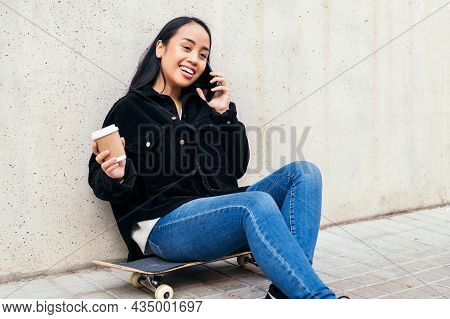 Smiling Asian Girl Talking By Phone Outdoors Sitting On Her Skateboard Leaning Against A Concrete Wa