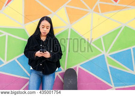 Young Asian Woman Typing On Her Phone Leaning Against A Colorful Wall Next To Her Skateboard