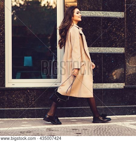 Young Stylish Woman Walking In Street. Woman Wearing Trendy Coat, Fashion Shoes And Holding Black Ha