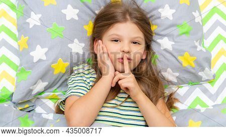 A Little Girl Is Lying In Bed And Pointing Her Fingers In Surprise. Be Quiet. The Girl Wants To Slee