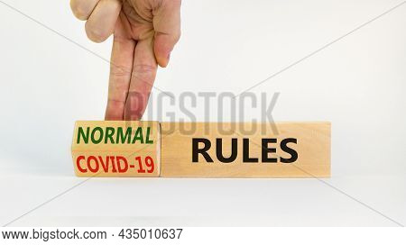 Symbol Of Covid-19 Or Normal Rules. Doctor Turns A Wooden Cube And Changes Words 'covid-19 Rules' To