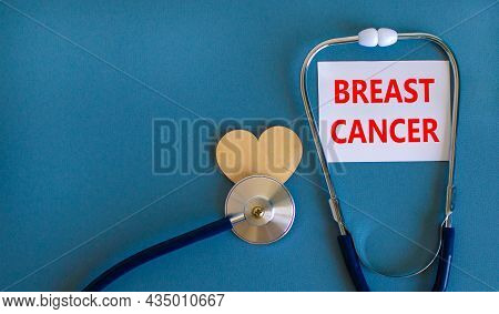 Breast Cancer Symbol. White Card With Words Breast Cancer, Beautiful Blue Background, Wooden Heart A