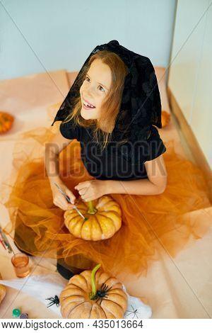 Little Girl Drawing Face On Orange Halloween Jack-o-lantern Pumpkin