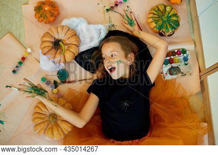 Top View Of Smiling Girl Lying On The Floor Between Drew Pumpkin Halloween