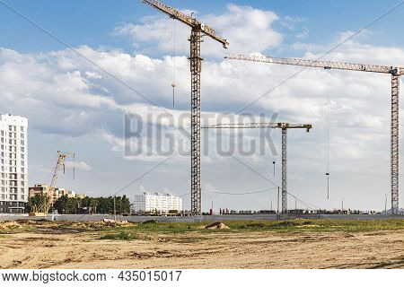 The Work Of Tower Cranes Against The Background Of The Sunset Sky. Modern Housing Construction. Indu