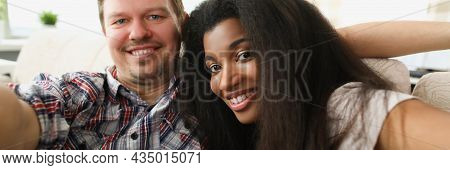 Cheerful Multiethnic Couple In Love Sits In Embrace In Cozy Living Room At Home