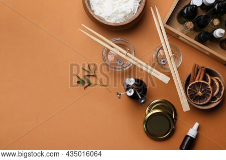 Flat Lay Composition With Homemade Candles Ingredients On Brown Background, Space For Text