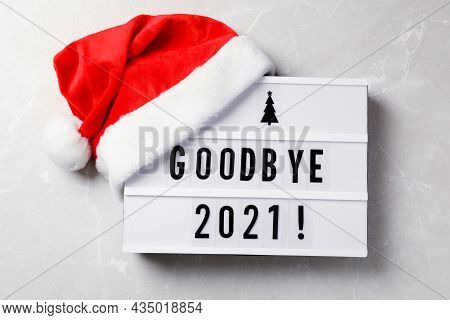 Lightbox With Text Bye Bye 2021! And Santa Hat On Light Grey Background, Flat Lay
