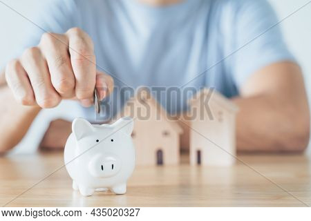 Man Hand Put Coin Into White Piggy Bank With Wooden House On Wood Table. Saving Money For Buying Hou