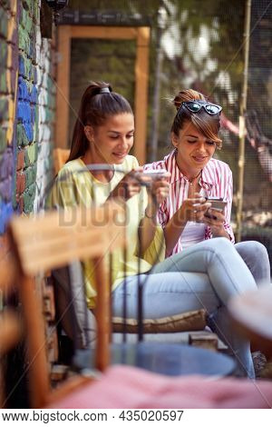 beautiful young adult female friends sitting one next to other in outdoor cafe, looking at their cell phones. social issue concept