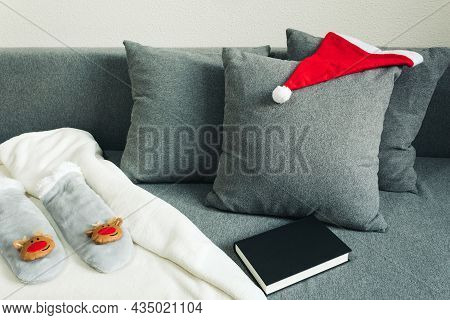 Blanket, Book And Warm Winter Clothes On A Sofa Indoors Alone. December And Christmas In Confined Ho