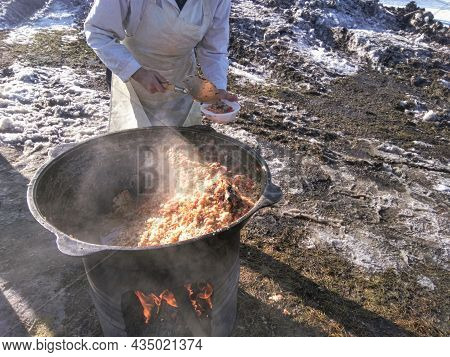 The Cook Cooks Food On The Street In A Cauldron In Winter On A Bonfire And Distributes It To The Nee