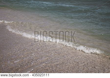 Background Of A Sandy Beach With Sea Waves. Foam From A Wave On The Sand. A Foamy Ocean Wave On A Se