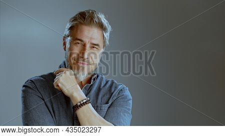 Portrait of happy older white man, beard gray hair, smiling. Copy space for text gray background,
