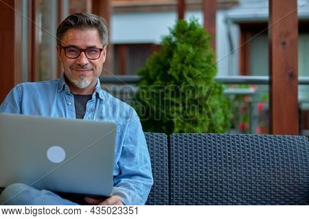Outdoor portrait of mid adult man in 50s, happy confident smile. Working with laptop computer in home office. Mature age, middle age, bearded.