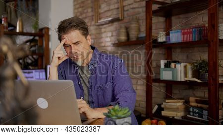 Mature man working in home office at a loft apartment, working from home online, using internet, thinking.