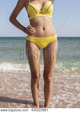 A Charming Sexy Woman In A Bikini Stands With Her Back To The Sea. Slim Girl In Yellow Swimsuit, Clo