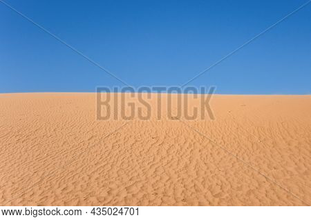 Ripple Sand Dunes And Blue Sky Background. Desert Landscape, Sandy Waves. Nature.