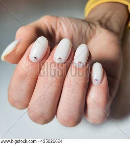 Gentle Gel Polish Of Milky Color On Short Nails With Sequins And Rhinestones. Nude Manicure With Dia