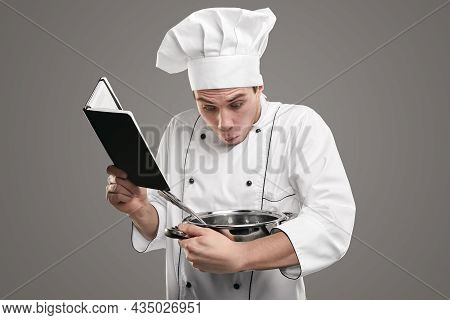 Stunned Young Man In Cook Uniform Holding Recipe Book And Looking Inside Saucepan In Stupor While Tr