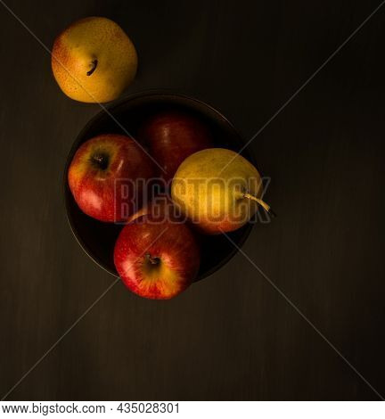 Still life food photography of fresh apples and pears. Top view of whole apple and pear fruits placed in a bowl on dark background.