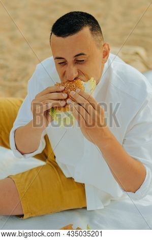 A Man Eats Food From A Delivery Service On The Beach From A Nearby Restaurant. Guy Eats Unhealthy Fo