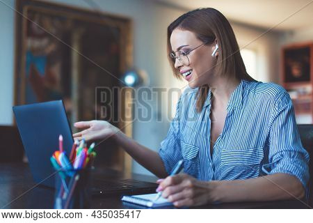 Young Entrepreneur Making Notes During Online Meeting Indoors