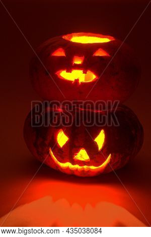 Halloween Pumpkin On Other Halloween Pumpkin. Mysterious Red Lighting And Reflections. Carved Scary