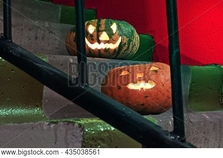 Two Jack-o'-lantern. Nice Pumpkins On The Stairs Behind The Bars Of The Railings